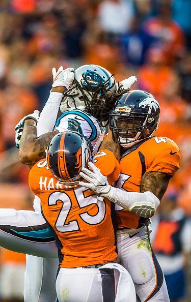 Denver Broncos cornerback Chris Harris Jr and safety TJ Ward attempt to stop…