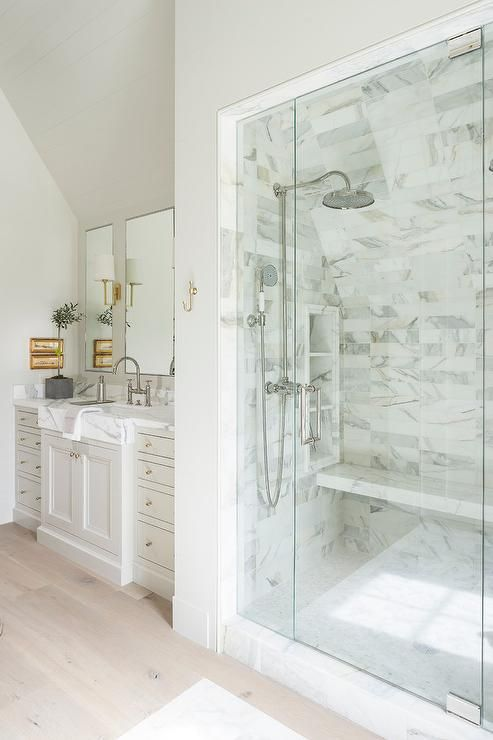 Under a slope ceiling, a light gray washstand donning small brass knobs and marble countertops fitted with a satin nickel deck mount faucet sat under inset vanity mirrors lit by brass sconces.
