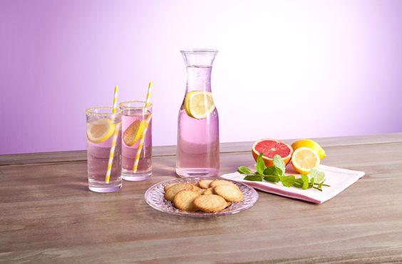 Pink Lemonade Was Sie brauchen: 220 Gramm granulierter Zucker 235 ml Wasser 580 ml frischer Zitronensaft 470 ml Cranberrysaft 318 Gramm feiner Zucker 3-4 Zitronen in Scheiben geschnitten 1,4 Liter Wasser Eiswürfel Essbarer Glitzer oder farbiger Zucker zum Verzieren Grapefruits als Dekoration