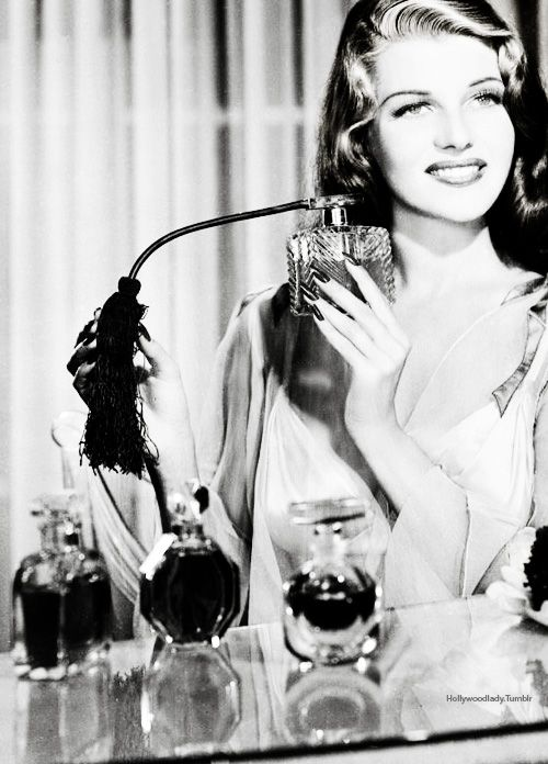 Rita Hayworth applying perfume: Glamour Magazine.: