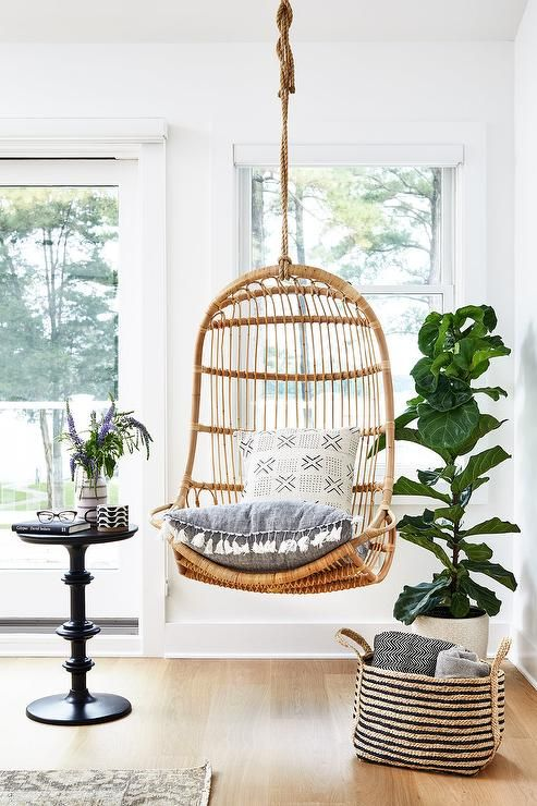 A Rattan Hanging Chair Accented With A Gray Tassel Cushion Is
