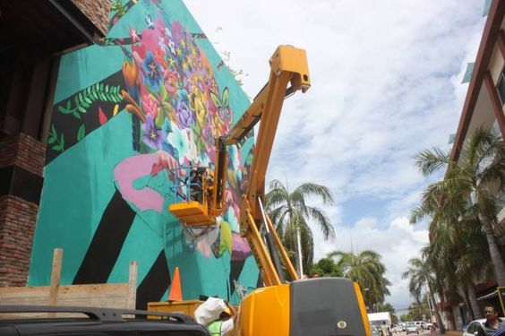 El artista urbano Senkoe realiza desde hace una semana un colorido mural en la pared de un edificio del centro de Playa del Carmen. (Daniel Pacheco/SIPSE)