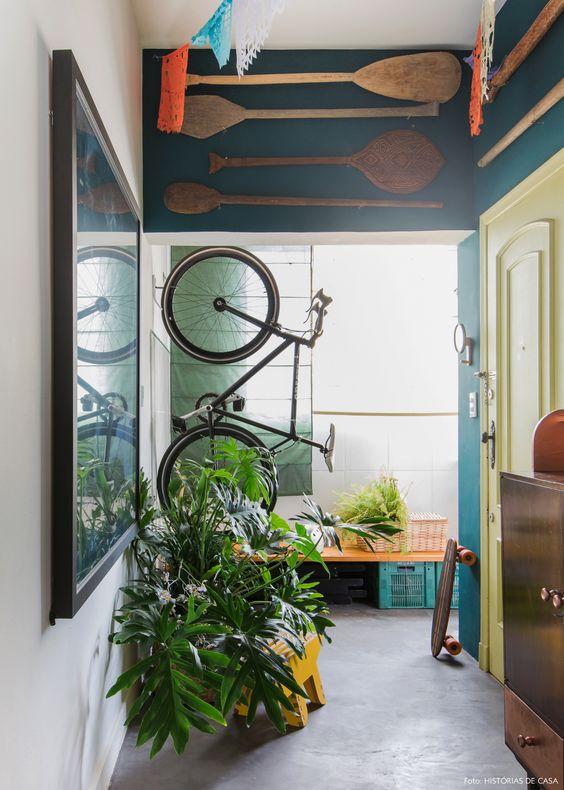 Hall de entrada de apartamento tem parede pintada de azul e bicicleta pendurada na parede.