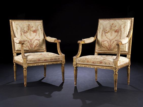Das Gestell jeweils reich beschnitzt und polimentvergoldet. Sitz und Lehne gepolstert, die in einem Schwung vorziehenden Arme mit kurzen Polsterstücken. Die ...
