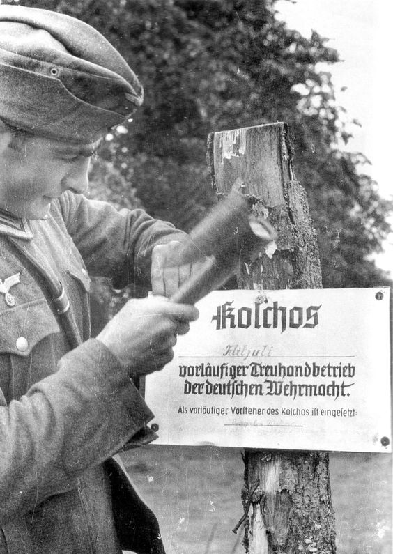 """The new proprietors: German soldier nails the sign that informs all that this particular Soviet Kolkhoz (collective farm) is now under the """"protection"""" (read: exploitation) of the German armed forces. From the beginning of the invasion of Russia, living off the land was the main German logistics plan given the poor communications and German shortages of food."""