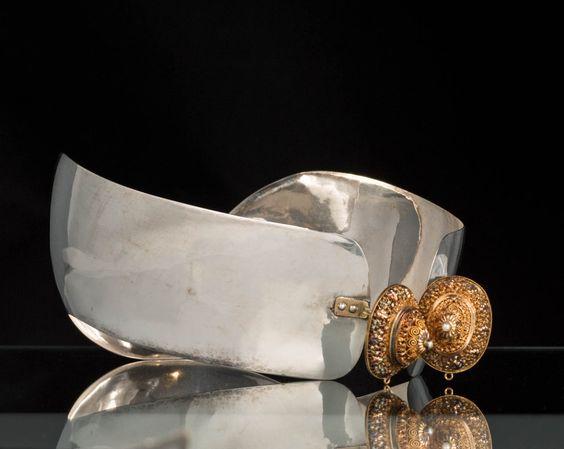 Zilveren oorijzer met knoppen in geel en rood goud en een pareltje. Het oorijzer is in 1919 vervaardigd door M.J.C.A. Hols uit Den Haag. Dit oorijzer is gedragen door een vrouw in streekdracht uit Scheveningen. #ZuidHolland #Scheveningen