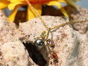 Chaîne et pendentif en or avec une perle de culture de Tahiti de qualité B semi-ronde de diamètre 9.35 millimètres de diamètre de couleur vert rose. Ce pendentif est accompagné de trois quartz.