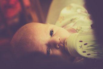 Baby mit offenen Augen wird mit Fläschchen gestillt