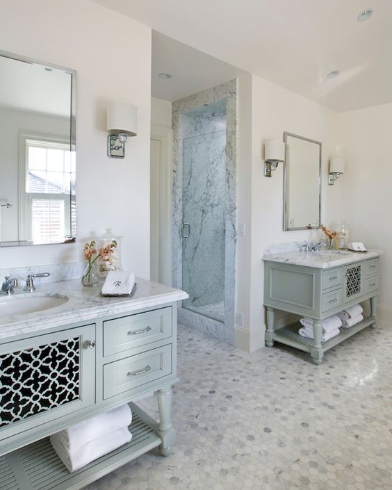 Sophisticated master bathroom features polished nickel mirrors over blue vanities with laser cut doors and turned legs topped with white marble countertops atop calacatta michaelangelo marble floor flanking doorway to walk-in shower and water closet.: