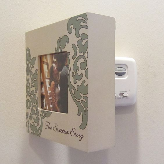 I covered my thermostat with a box picture frame given to us as a Wedding gift. I used a simple 3-screw, swinging brass bracket to secure it to wall. Much cuter! PS It doesn't mess with the internal temp readings of our home, but I would be careful with this. A thermostat that produces some heat should probably not be covered.