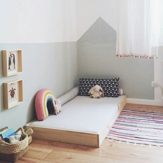 Montessori bedroom with floor bed, minimal toys and art hung low on the wall.