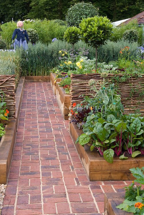 Beautiful Vegetable Garden With Brick Walkway And Raised Beds