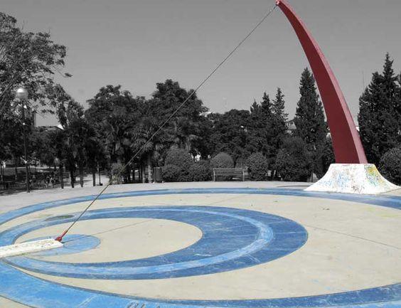 La hora la marca un cable sujeto a lo alto de un mástil curvo de hierro, cuya silueta evoca la mitad superior de un arco en tensión. Parque de La Granja. #Zaragoza