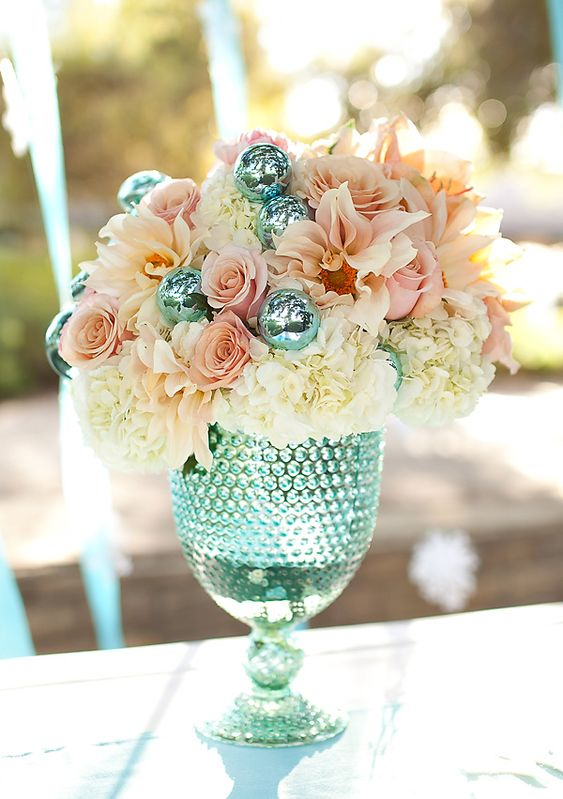 Blue tinted glass vase filled with blush toned flowers and decor.  This would be beautiful at a wedding reception!