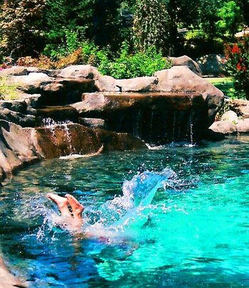 The water flowing from the waterfalls in this elegant swimming ...