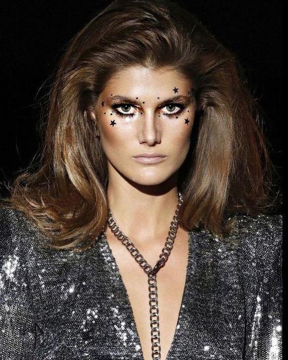 Modelo de pasarela maquillada con estrellas en torno a los ojos, pelo largo con volumen, moreno