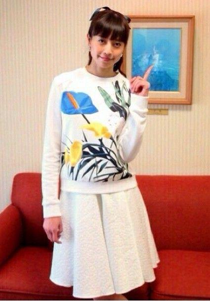 花のイラストが描かれたシャツに白いスカートをはいた片瀬那奈の画像
