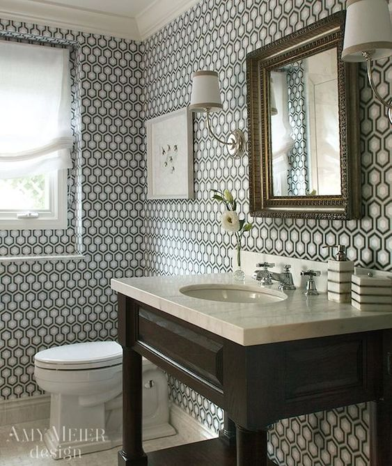 Chic powder room boasts walls clad in Hicks Hexagon Wallpaper framing a pair of Vendome Single Sconces which flank an antique gilt mirror over an espresso stained sink console topped with a marble counter and undermount oval sink with hot and cold faucet.