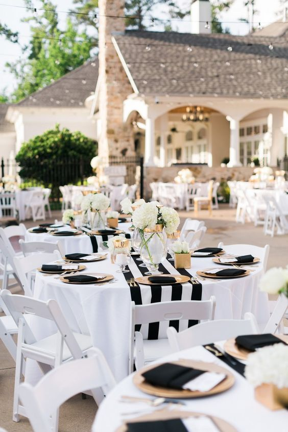 Backyard party Gold chargers, black napkins with menus, black + white stripe runners