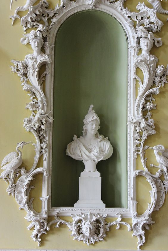 Niche in the North Hall at Claydon House,Buckinghamshire,c.1760carved by Luke Lightfoot. The large niches in the walls have frames of carved wood with writhing foliage that contains human heads and exotic or heraldic birds, notably wyverns and cranes. These niches originally contained marble busts of the continents of Africa, Asia, Europe and America.