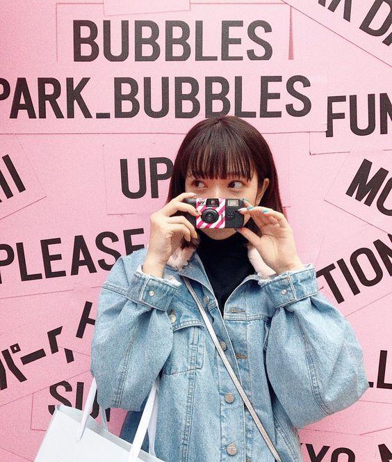 ピンクの可愛い背景の前で写真を撮る田中芽衣