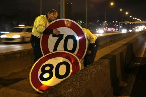 """Not So Fast          On a highway encircling Paris, city workers replace an 80 kphspeed limit sign with a 70 kph oneon Jan. 7. The controversial speed limit change was done, officials said, to lessen the amount of noxious gases emitted by vehicles at high speed and reduce polluting traffic jams. In December, officials in Paris issued an air pollution alert as """"cold weather entrapped diesel fumes, leading to the most severe smog in the French capital since 2007,"""" reported Bloomberg…"""