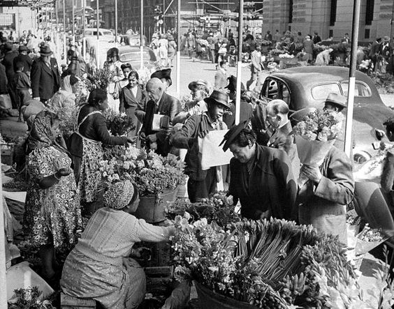 Busy scene on the pavement in front of the Post Office.  The flower sellers in Parliament Street 1946