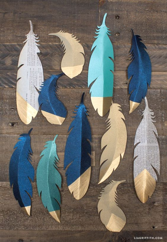 Dipped gold paper feathers to use as Christmas wrapping embellishments
