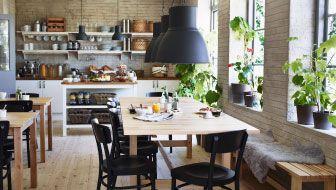 Stanza per la colazione di un B&B arredata con tavoli in betulla massiccia e sedie nere