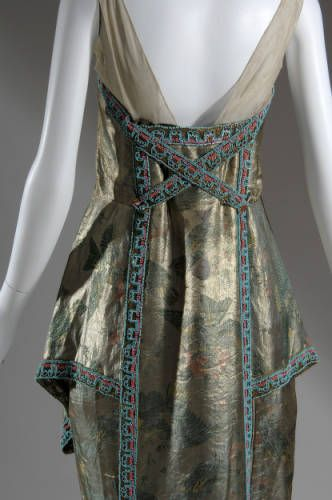 1926.Dress (a), evening-style, with net shoulder straps. Large pendant of pearls and beads hangs from neckline at front. Detachable train (b) of metallic brocade printed with birds and flowers in orange pink and green. Neckline, skirt, and train all edged with bands of blue green and orange pink beads.