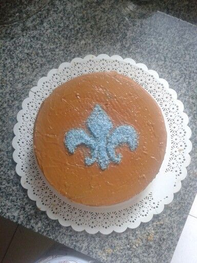 Vainilla cake, filled and covered with dulce de leche, and a coconut fleur de lis decoration.