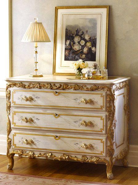 Un clásico, cómoda con cuadros de flores clásicas enmarcada con moldura dorada y passpartout con dibujos dorados.