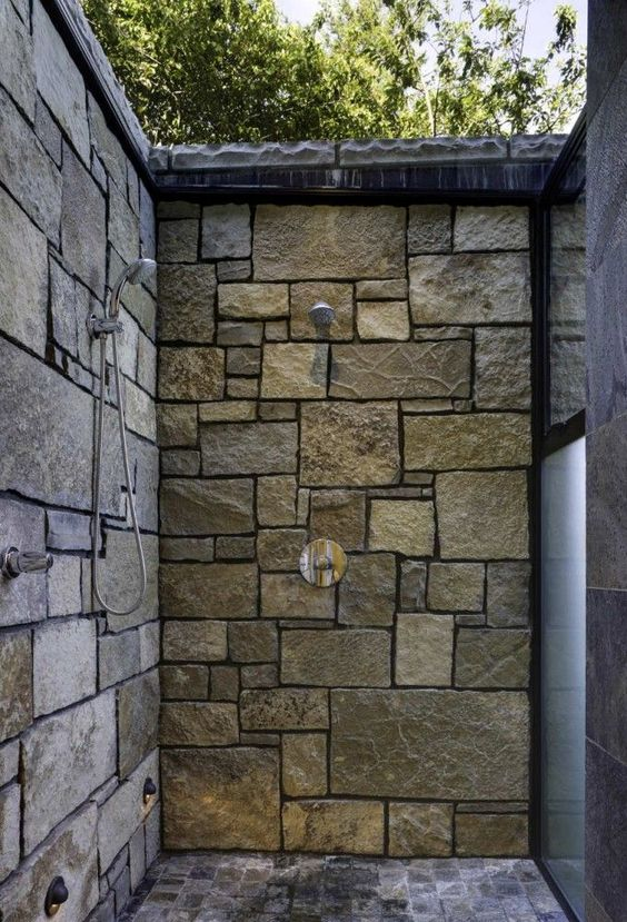 This Washington state shower uses stacked stones to protect against and blend into the elements.