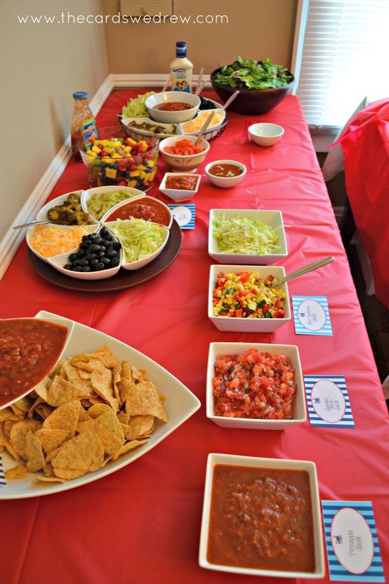 Shredded lettuce, salsa, refried beans, diced tomatoes, cheese, meat, sour cream, and fruit salad.