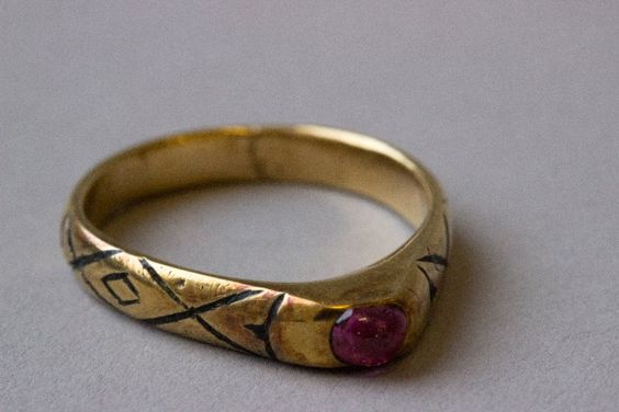 Finger-ring; gold; the shoulders engraved and nielloed with a lozenge design; shoulders rise to pointed bezel set with ruby. Date13thC-14thC