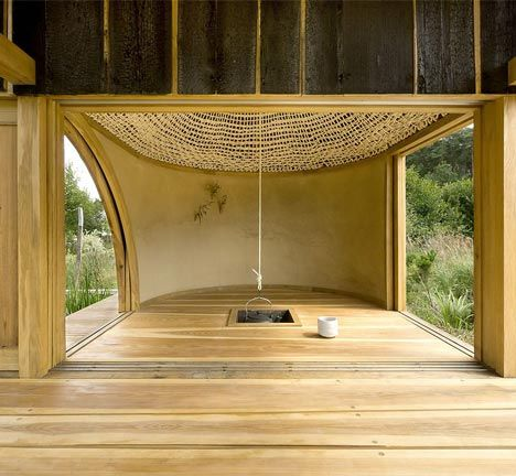 Visitors to this timber tea house sit beneath a woven rope dome with a gilded skylight and a hanging teapot in the middle.: