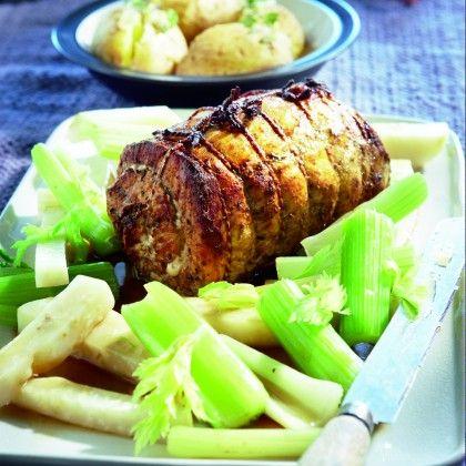 Leg de rollade op een rooster boven de braadslee met bouillon in de oven. Voeg het marinadevocht bij de bouillon en leg de knolselderij en bleekselderij erin. Boen de aardappelen schoon onder warm water en prik de schil hier en daar in. Verpak ze in aluminiumfolie en leg ze de laatste 50 minuten naast de rollade in de oven. Rooster het vlees in 75 minuten gaar en bruin. Bestrijk het de laatste 15 minuten met de honing. Snijd het vlees in plakken. Serveer de gepofte aardappelen erbij. Schep…