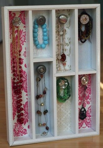 Jewellery organised in DIY cutlery divider with door knobs and scrapbook paper backing.