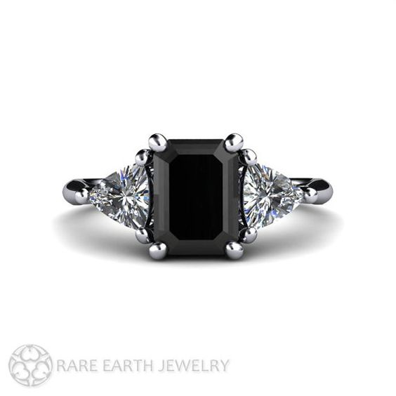 An absolutely stunning vintage inspired black diamond three stone ring in Platinum. The black diamond is approximately 1.15 carats and is surrounded by