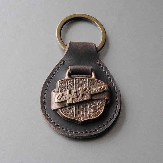 Llavero de cuero vaquetilla envejecido con anilla en oro viejo. El logo del escudo de Café Racer Obsession está modelado y fundido en bronce por Valtorón, de manera artesanal y artística.  1OO% Handmade in Madrid.