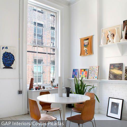 Der runde Tulip Tisch fügt sich durch seine schlichte Eleganz nahtlos in das Esszimmer dieser Altbauwohnung ein. Die braunen Stühle, die an alte Schulstühle  …