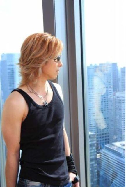 黒いタンクトップで外を見ているXJAPAN・YOSHIKIの画像