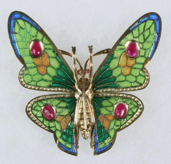 """BROOCH - 18K Yellow Gold, Plique-a-jour, Opal, Ruby & Diamond Butterfly Form Brooch, plique-a-jour wings are set with (4) oval faceted rubies and are lined with small diamonds, body is set with a round opal, small diamonds, and (2) small ruby eyes; 2 1/4"""" x 2 3/8"""", 11.6 dwt tw; fine condition."""
