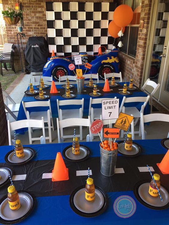 Hot wheels themed tablescape with flag backdrop two fondant covered cakes with cream cheese filling with a track passing thru the cake cake pops mini cupcakes and sugar cookies children decorated tables for a birthday party