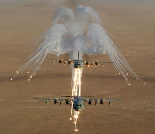 Two US Marine Corps KC-130 Hercules firing flares used for protection against surface-to-air missiles in Iraq.