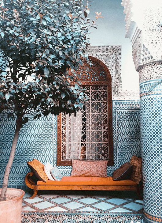 Patterned tiles as background to single tree and daybed. Peaceful and beautiful.