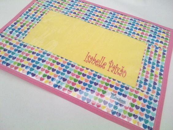 Lugar Americano confeccionado em tecido 100%, com forro em feltro, revestimento superior em plástico cristal e acabamento em viés. <br>Pode ser personalizado com nome da criança bordado à máquina. <br> <br>*As cores podem ser escolhidas. Consulte disponibilidade.