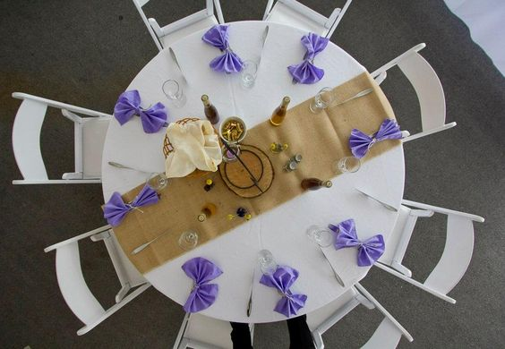 Burlap makes an incredibly affordable and natural table runner and makes any color of linens or flowers placed ontop really pop. The favors at this wedding were also creative - wine made by the bride & groom.