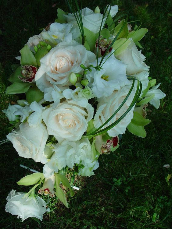 Cascade bouquet with white roses, lisianthus, green cymbid orchids.