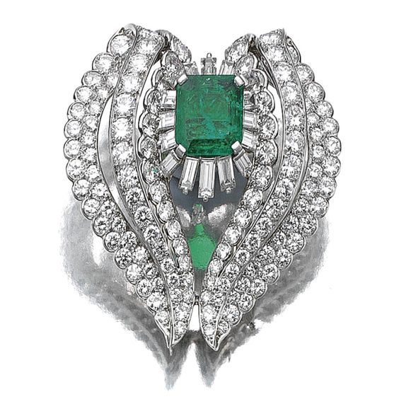 EMERALD AND DIAMOND CLIP, MONTURE CARTIER, 1950S. Centring on a rectangular step-cut emerald set within a baguette diamond ballerina border, flanked by two curved motifs set with brilliant- and circular-cut stones, mounted in platinum, signed Monture Cartier, French assay and maker's marks.